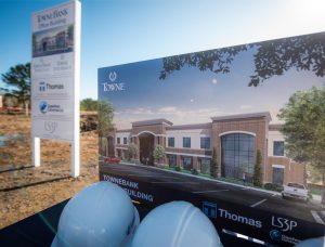 Photo of building rendering and hard hats at groundbreaking event.